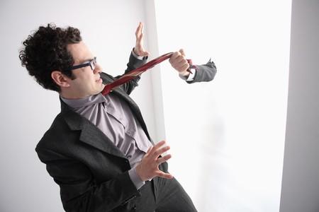 southern european descent: Hand pulling businessmans necktie Stock Photo