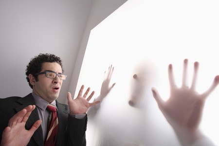 Businessman frowning while looking at silhouette of a man behind transparent paper Stock Photo - 6990653