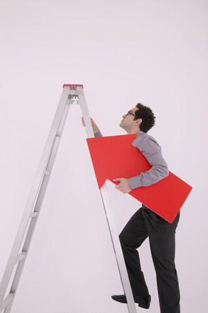 Businessman holding arrow sign while climbing up ladder photo