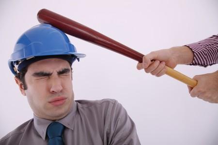 safety helmet: Hombre de negocios con casco de seguridad, cerrar los ojos al ser golpeado con un bate de b�isbol