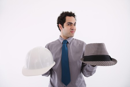 Businessman holding fedora and safety helmet photo
