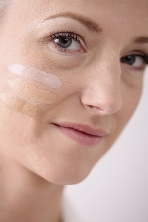 Woman with three stripes of liquid foundation on her face Stock Photo - 6990674
