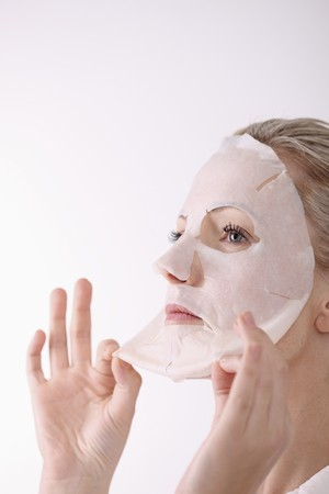 removing: Woman peeling off her facial mask Stock Photo