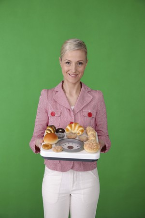 Woman weighing pastries on weight scale Stock Photo - 6990678