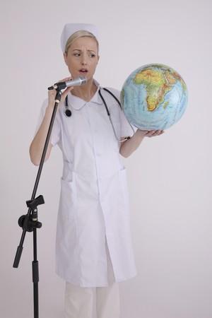 Nurse talking into microphone while holding globe photo