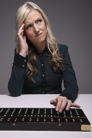 Businesswoman thinking while using abacus photo
