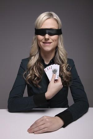 Blindfolded businesswoman holding playing cards Stock Photo - 6990691