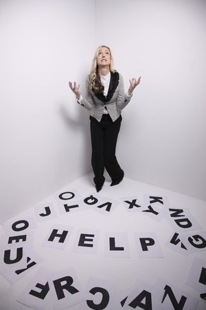 Businesswoman looking up, the word HELP being arranged on the floor photo