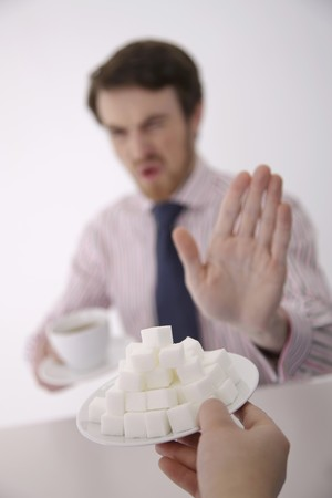 """Man showing hand gesture saying """"No"""" at the offer of sugar cubes Stock Photo"""