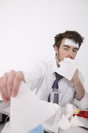 Man having flu and fever reaching for more tissue photo