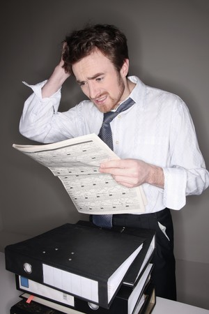 Man reading newspaper while scratching his head Stock Photo - 6990714