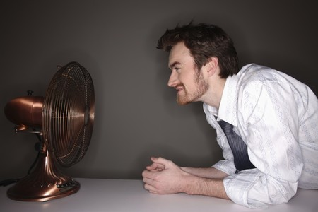 Man sitting in front of electric fan Stock Photo - 6990716