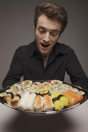 Man holding a plate of sushi set Stock Photo - 6990718