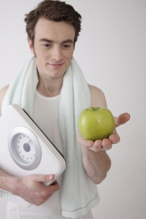 Man holding scale and a green apple photo
