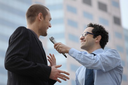 southern european descent: Man holding microphone interviewing businessman