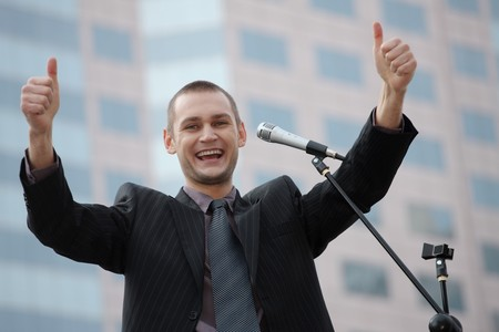 speaker: Businessman showing thumbs up while giving speech Stock Photo