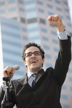 public speaker: Businessman raising his hand while giving speech Stock Photo