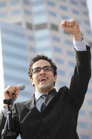 southern european descent: Businessman raising his hand while giving speech Stock Photo