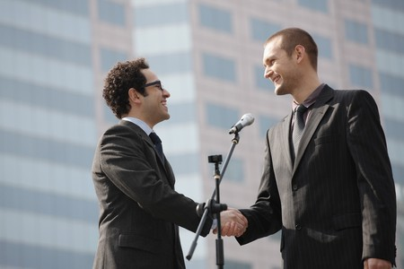 Businessmen smiling while shaking hands Stock Photo - 6990737
