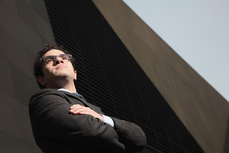 Businessman folding his arms while looking away photo
