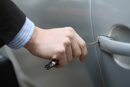 Businessman unlocking car door photo