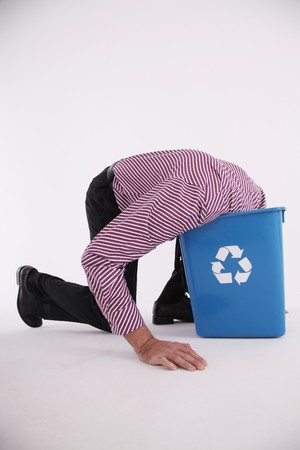 eastern european ethnicity: Businessman putting his head into the recycling bin Stock Photo