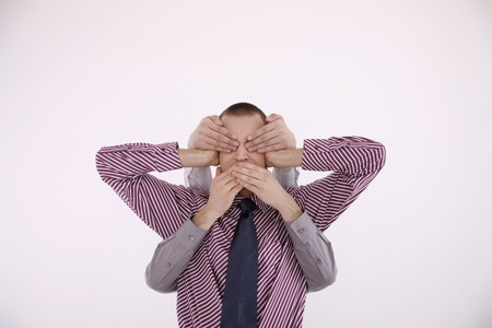 covering: Businessman covering ears, another two pairs of hands covering his eyes and mouth Stock Photo