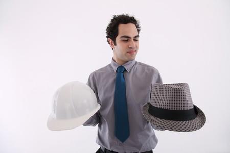Businessman holding fedora and safety helmet Stock Photo - 6990762