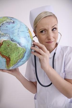 Nurse using stethoscope on globe photo