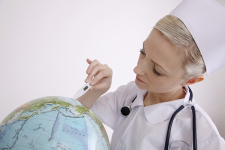 Nurse using thermometer on globe photo