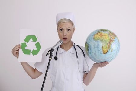 Nurse holding globe and recycling symbol while talking into microphone photo