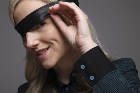 blindfolded: Businesswoman peeking under blindfold Stock Photo