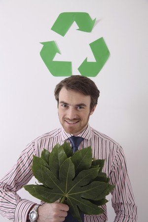 Man holding leaves with recyling symbol above his head Stock Photo - 6990801