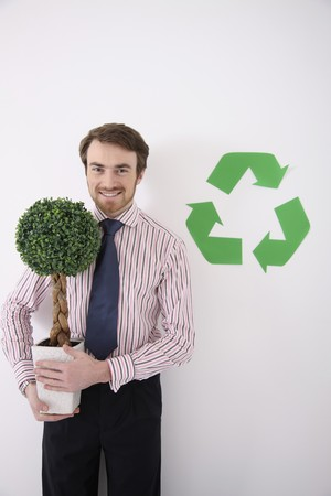 Man holding potted plant with recycling symbol at the side Stock Photo - 6990802