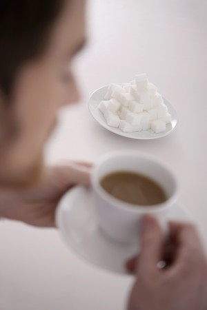 Man enjoying a cup of coffee, focus on sugar cubes on the table Stock Photo - 6866673