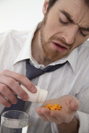 north western european descent: Man pouring pills from plastic bottle Stock Photo