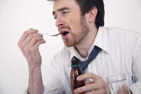 cough medicine: Man taking cough medicine Stock Photo