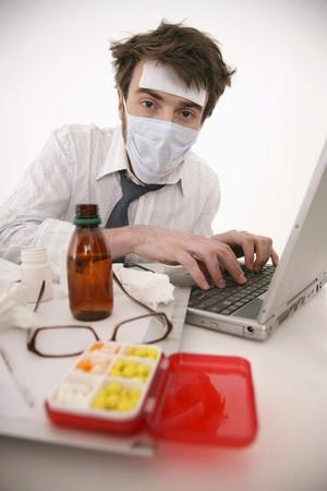 north western european descent: Sick man working on laptop