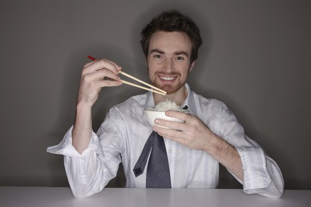 north western european descent: Man eating rice with chopsticks Stock Photo