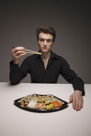 Man holding chopsticks with a plate of sushi on the table Stock Photo - 6990821