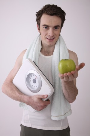 Man holding scale and a green apple Stock Photo - 6990825