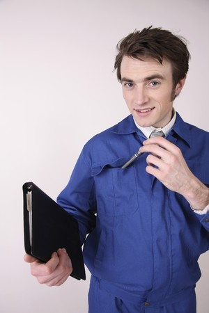 Man holding organizer putting pen into coveralls pocket Stock Photo - 6990835