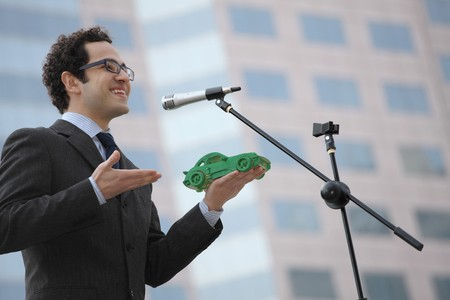 car model: Businessman holding a green car model while giving speech