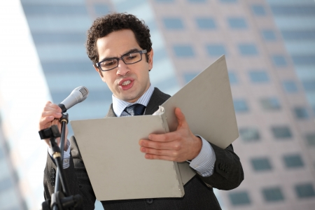 southern european descent: Businessman reading speech from document Stock Photo
