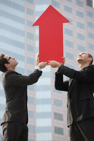 Businessmen with arrow sign pointing up photo