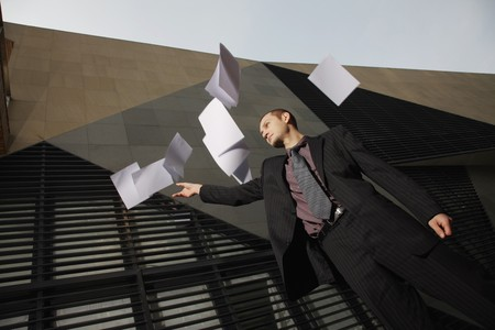 Businessman throwing sheets of paper in air photo