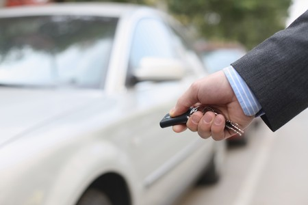 southern european descent: Businessman unlocking car Stock Photo