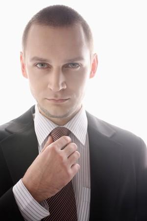 Businessman adjusting his necktie photo