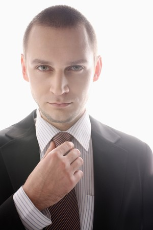 Businessman adjusting his necktie photo