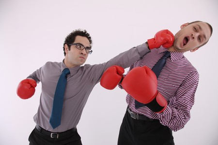 people fighting: Businessman with boxing gloves punching man in the face